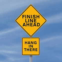 Road sign: Finish Line Ahead; Hang in There